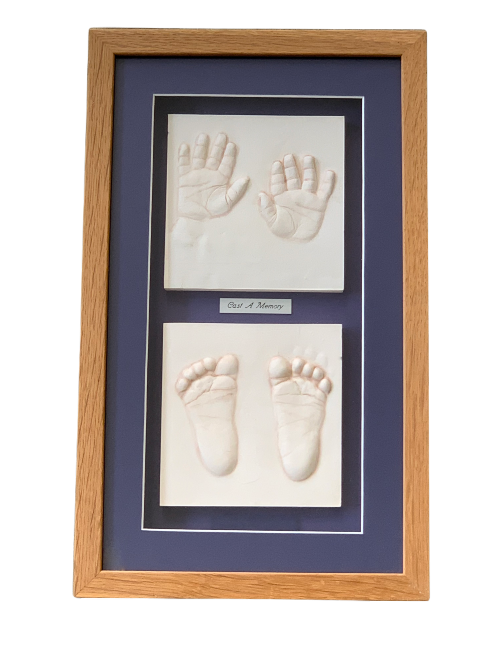 clay hands and feet impressions in a light wood frame