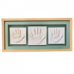 Clay hand impressions of siblings in a light wooden frame