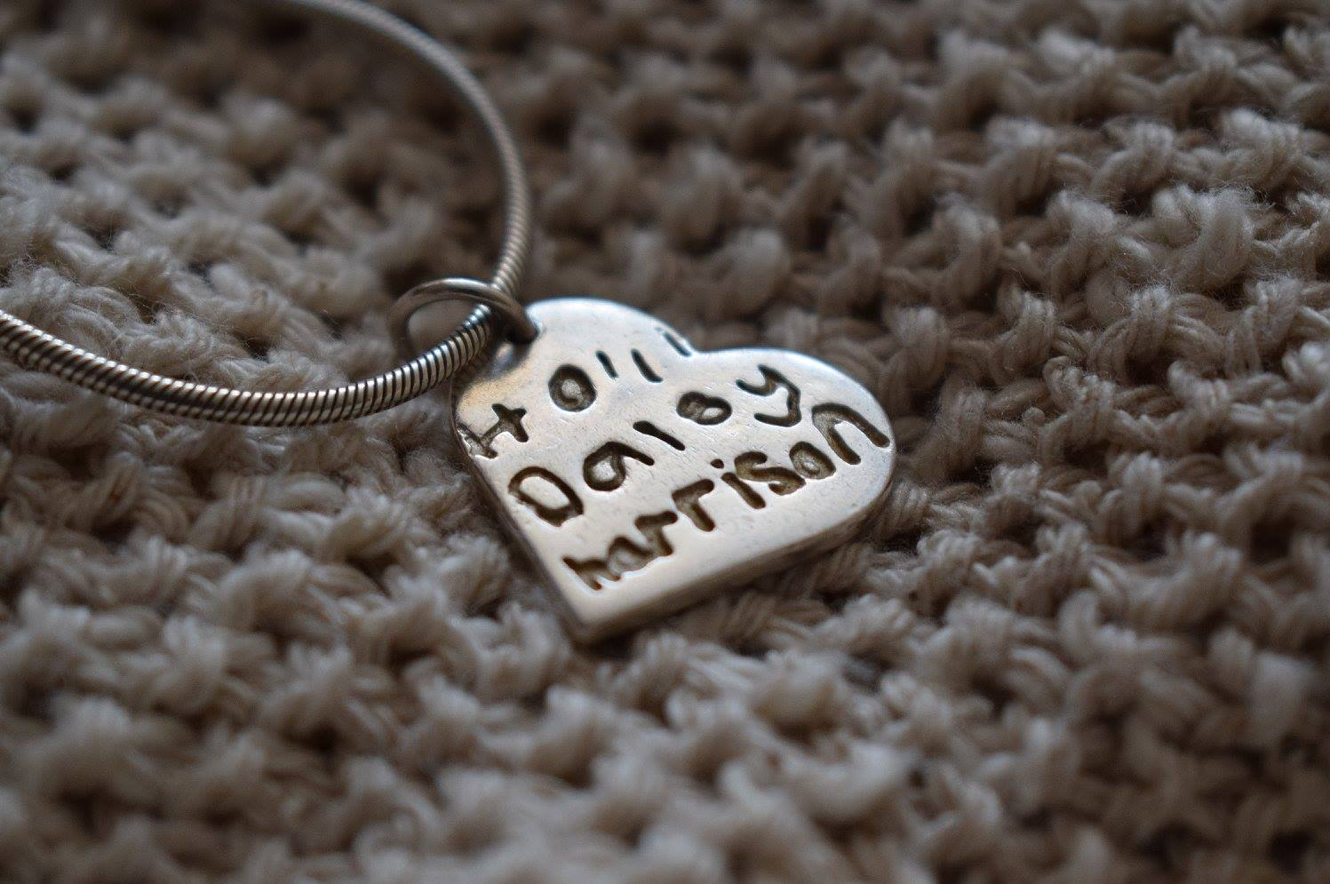 childrens name inscribed on a silver necklace charm