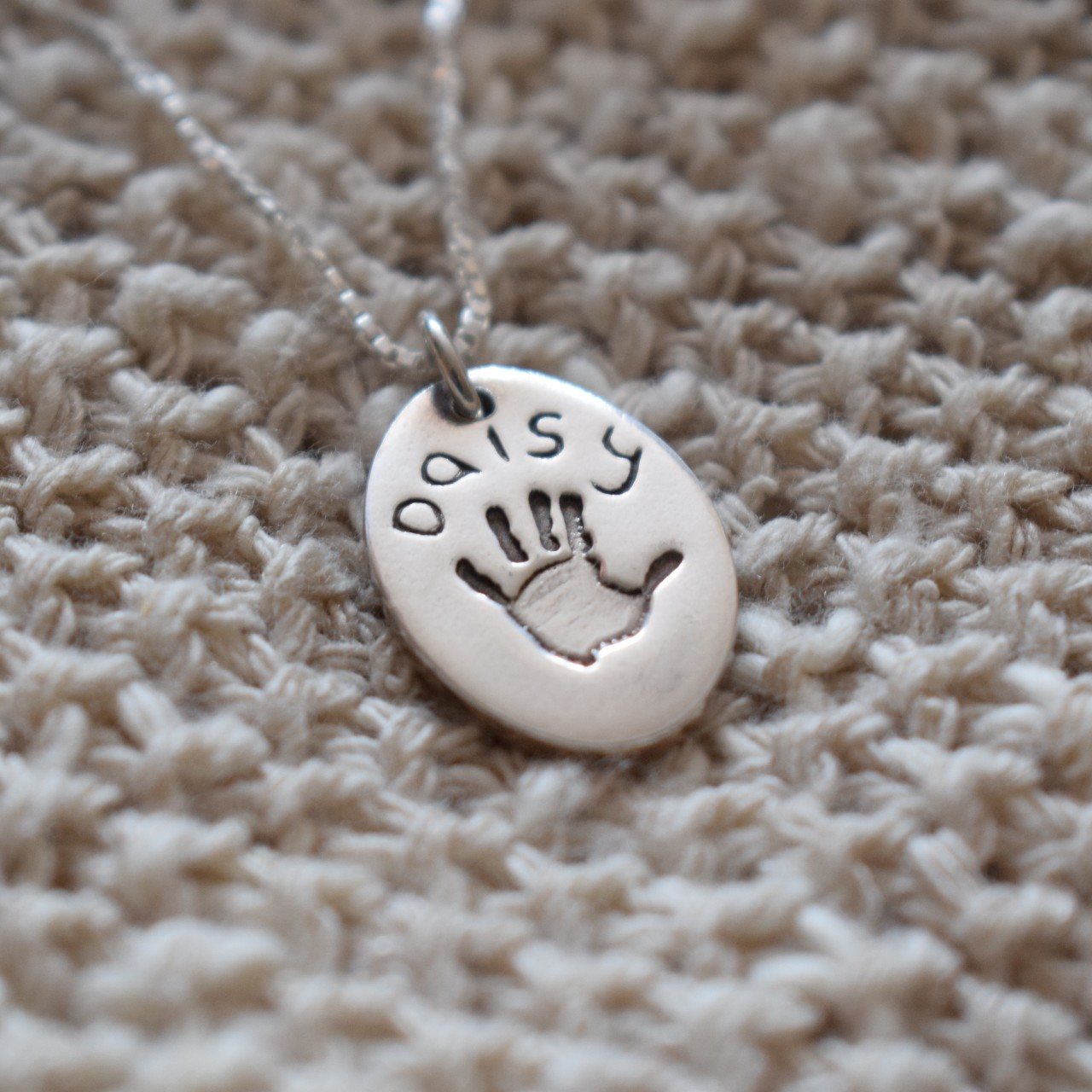 oval charm with handprint and name